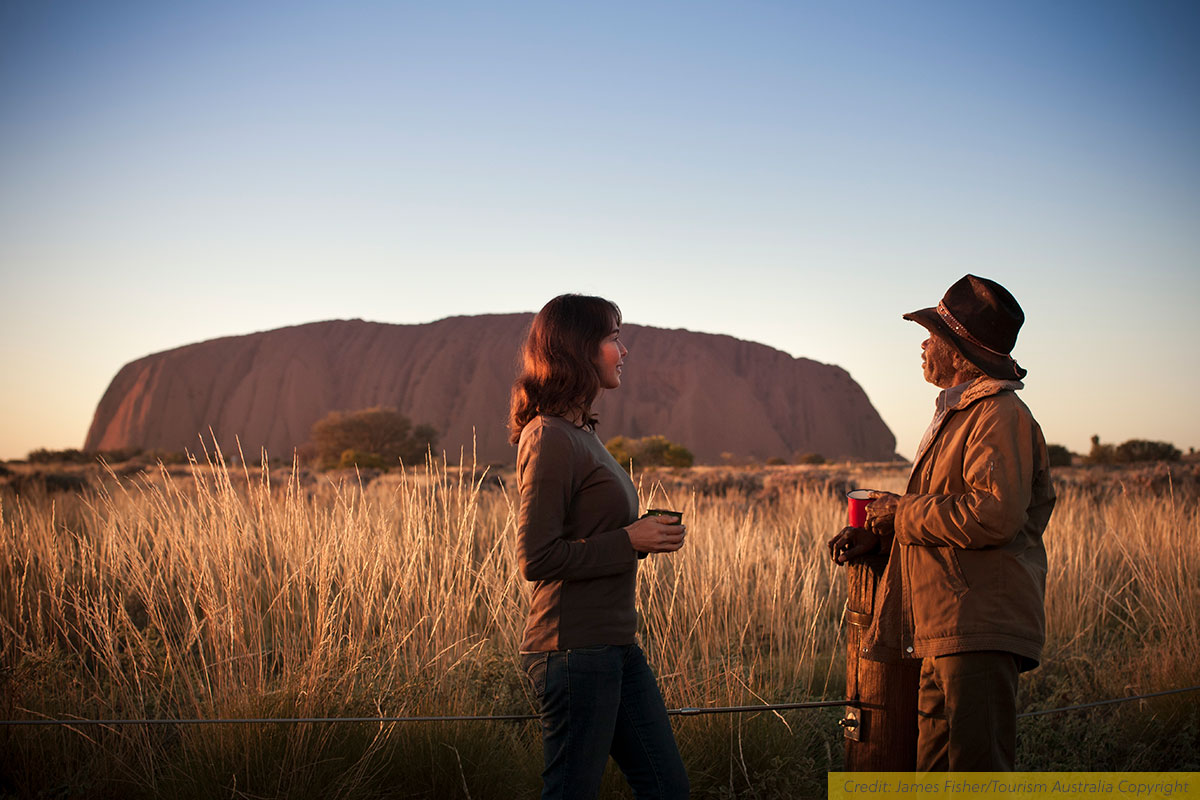 A female traveller talks to an Aboriginal guide on a tour in Uluru/Kata-Tjuta National Park, NT, Australia