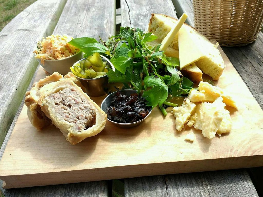 Ploughman's lunch - a traditional English snack or lunch with cold meat, cheeses, pickles and fresh bread.