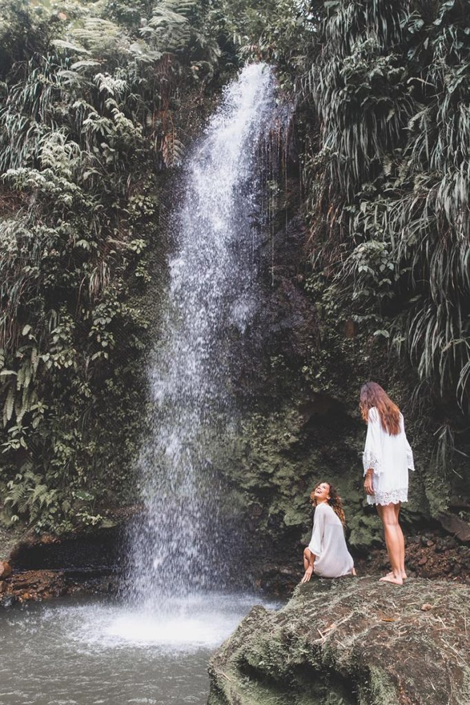 Two female travellers explore Saint Lucia waterfall