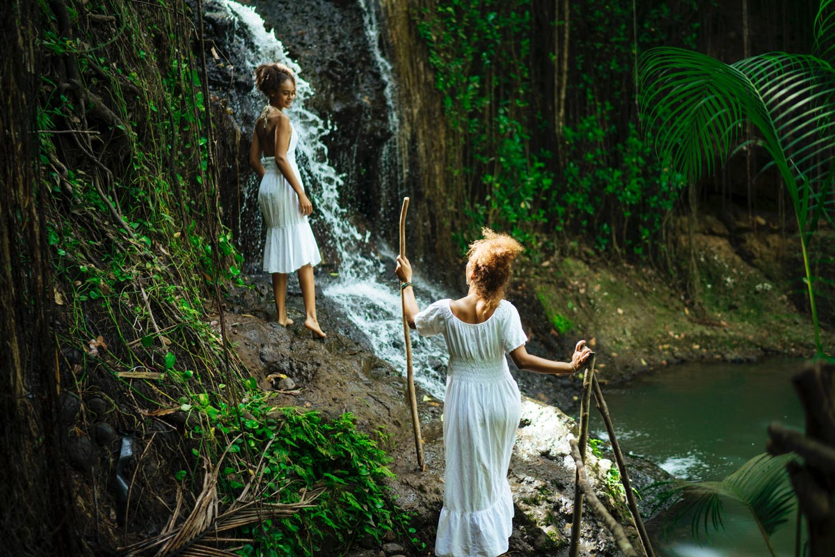 Two female travellers discover a waterfall in Saint Lucia's tropical rainforest